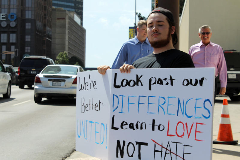 A man held a handwritten sign on the sidewalk outside the Meyerson.