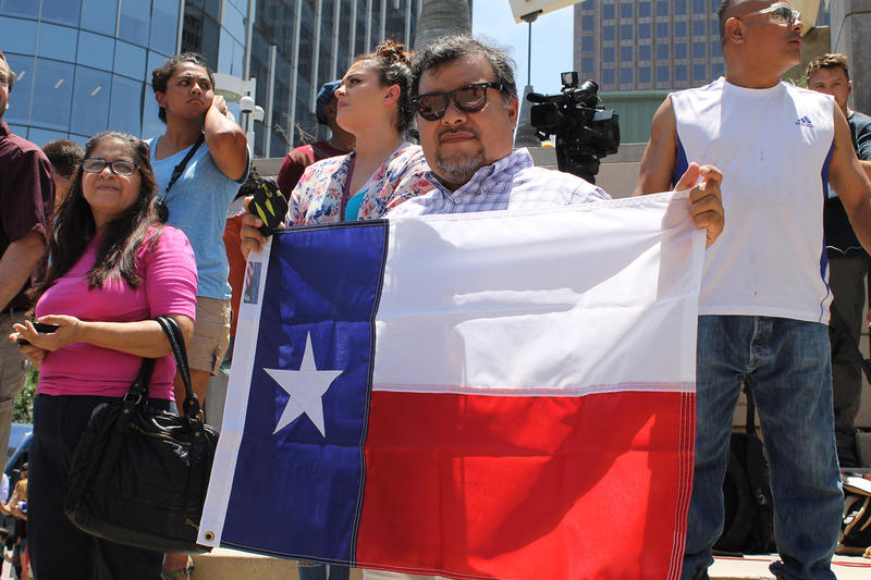 A man holds a Texas flag outside of the Morton H. Meyerson Symphony Center in July during a memorial service for the five fallen Dallas police officers.