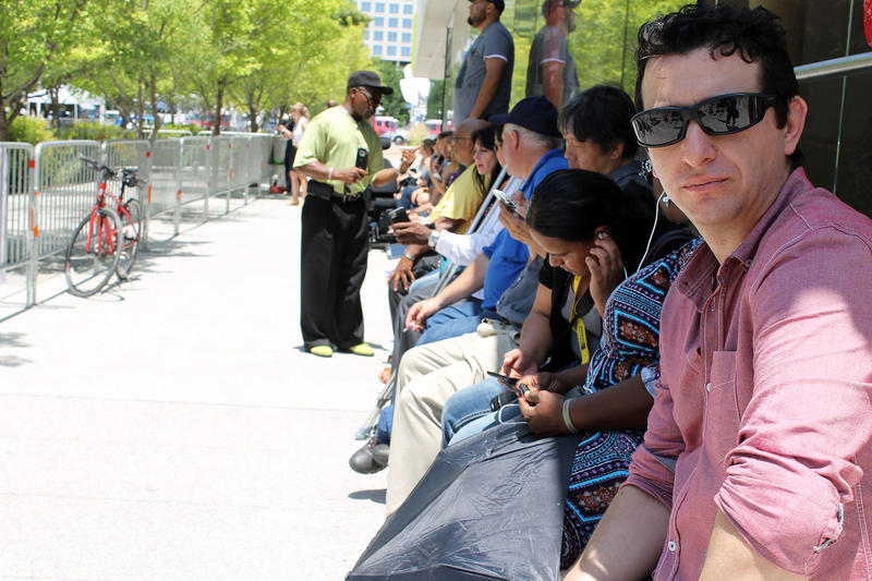 People sat along a building across from the Meyerson and listened to the broadcast of the service.