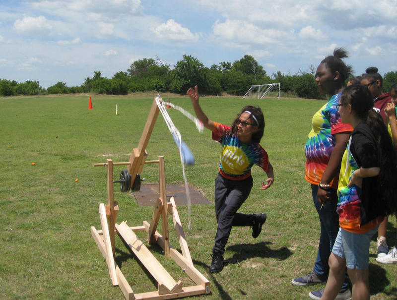 The Perot Museum's TECH Truck trebuchet in action.  Science students launched apples, tangerines and tomatoes. One apple ended up 117 feet downfield.
