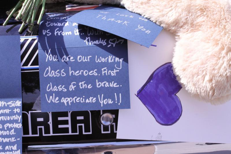 Notes on the police cars express an outpouring of support for the officers.