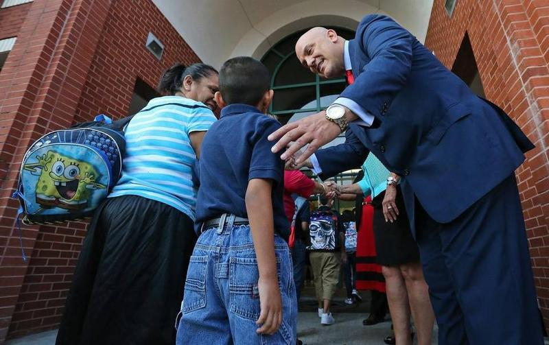 Fort Worth Superintendent Dr. Kent Scribner greets parents and students at the front door as school children returned to school last yearat Diamond Hill Elementary.