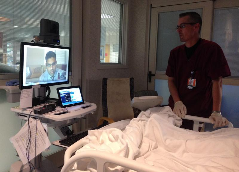 Robb Sexton, RN at Hopkins County Memorial Hospital in Sulphur Springs, sets up Dr. Pritam Ghosh (on screen) to examine a patient in the ICU.