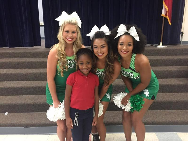 Jordan Phipps, 8, and cheerleaders from the University of North Texas. Phipps was awarded a $10,000 scholarship for and admittance to UNT on Thursday.