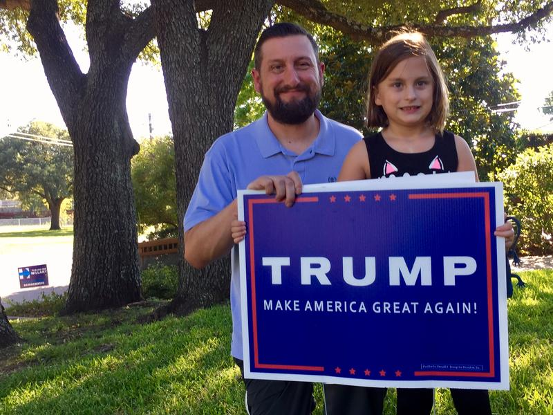 "JP and Ada Morgan pose with their Donald Trump campaign sign. To the left, you can see their neighbor Melanie Grimes' ""Texans For Hillary"" sign."