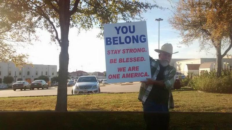 A man holds a sign outside the Islamic Center of Irving on Nov. 26, 2016.