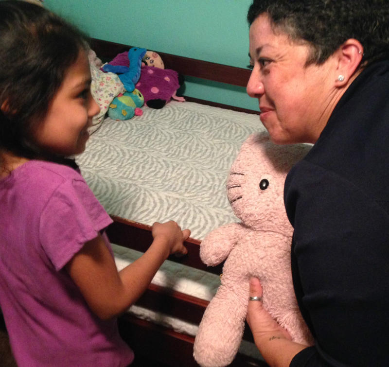 Sarai (left) shows off her house, room and favorite doll to 2nd grade teacher Esther Martinez. Sarai's had the doll since she was just months old.