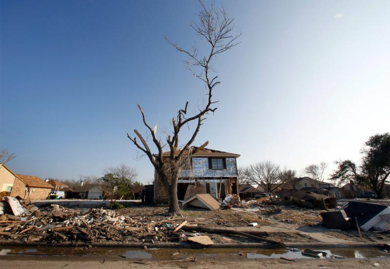 "A house, a damaged tree and debris in a Rowlett neighborhood in February 2016, two months after the tornadoes. Explore more: <a href=""http://stories.kera.org/rebuilding"">Rebuildling A Life: A Year Later</a>."