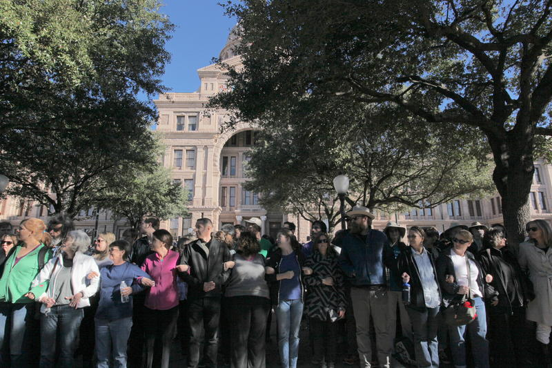 Supporters link arms outside the capitol to block protestors on Texas Muslim Capitol Day.