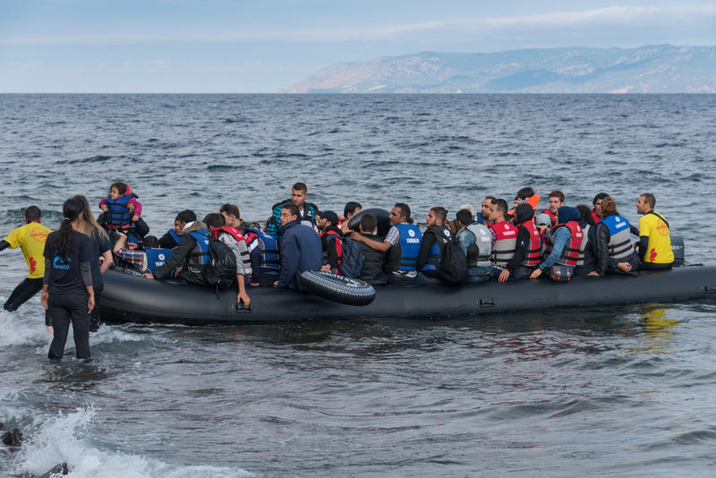 Refugees, escaping war and Islamic State, arriving in Greece by boat from Turkey. Volunteer lifeguards assist and guide the boat to shore when the motor failed.