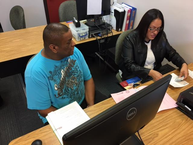 Brodney Benson works with Arlington VITA program coordinator Maricela Avila.
