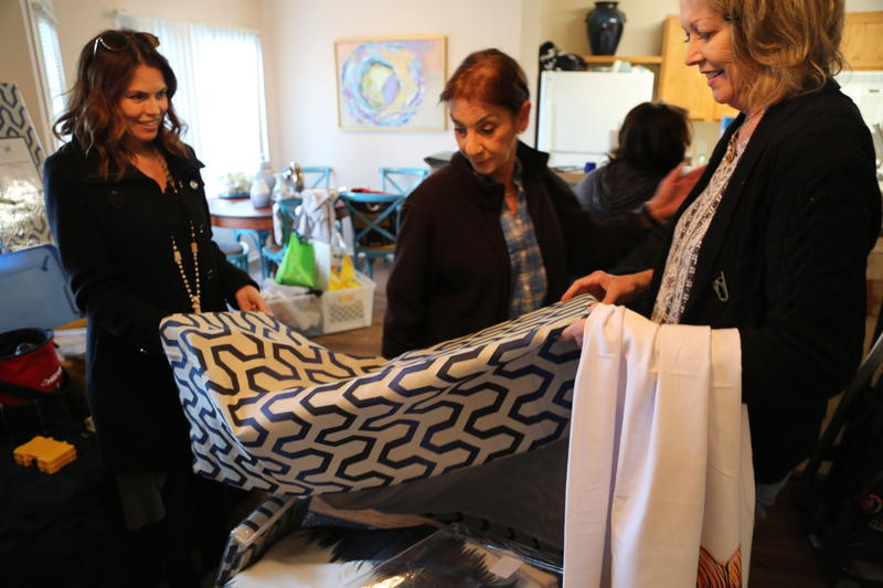 Dwell With Dignity Founder Lisa Robison (left) and Vice President Kim Turner (right) admire drapes with volunteer.