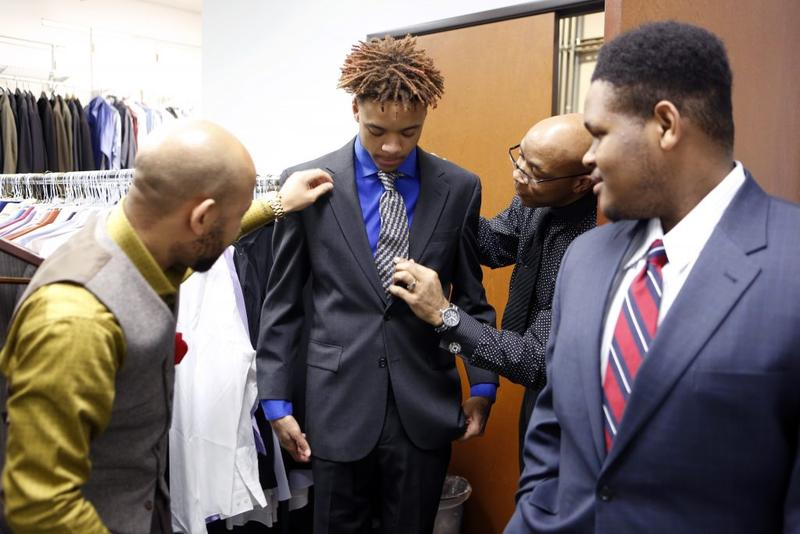 Kimball High School Academy of Hospitality and Tourism students are fitted with suits to interview in while on a field trip to Workforce Solutions Greater Dallas.