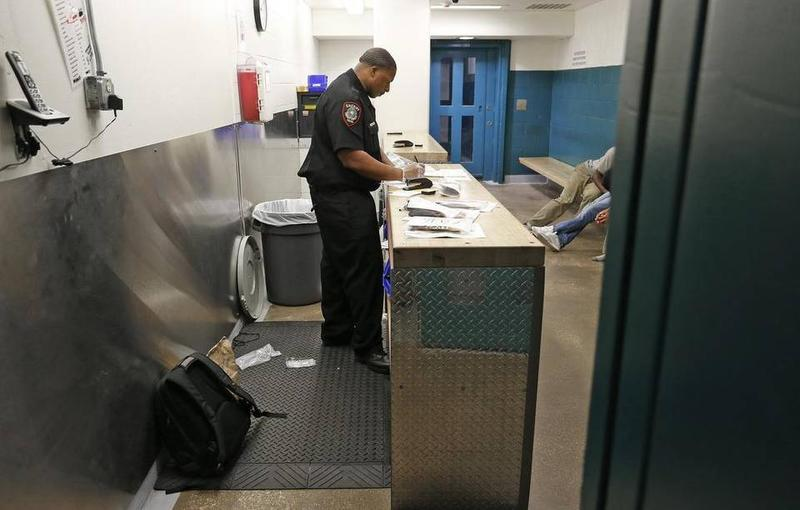"A Tarrant County detention officer logs inmates into the jail in the ""back door"" section of the jail, the first step of processing."