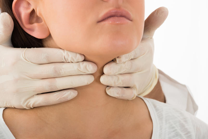 A doctor performing physical exam palpation of the thyroid gland.