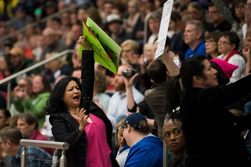 Attendees hold up signs in the bleachers at a town hall meeting in Flower Mound held by U.S. Rep. Michael Burgess, R-Lewisville on March 4, 2017.