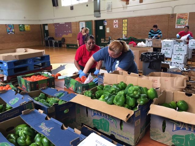 Parent volunteers sort and bag produce at John Quincy Adams Elementary.