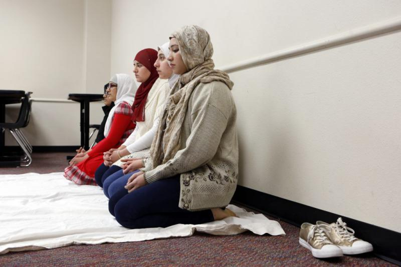 Amna Salman (foreground) and other Muslim students gather to pray inside a classroom at Liberty High. Photo/Lara Solt