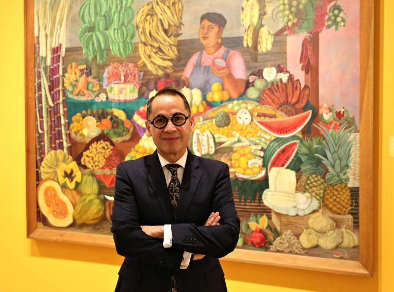 "The New DMA Director Agustin Arteaga posing in front of Olga Costa's ""The Fruit Seller."""