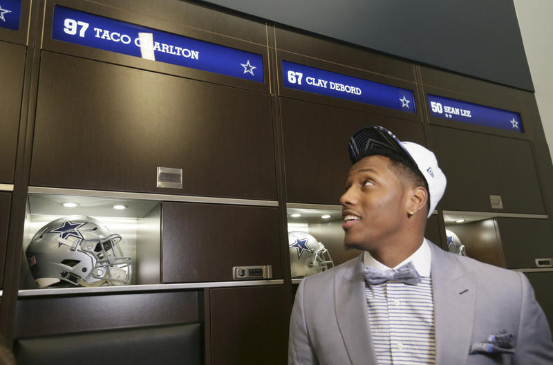 The Dallas Cowboys' No. 1 draft pick, defensive end Taco Charlton, looks at his new locker at the team's football headquarters in Frisco, Texas, Friday, April 28, 2017.