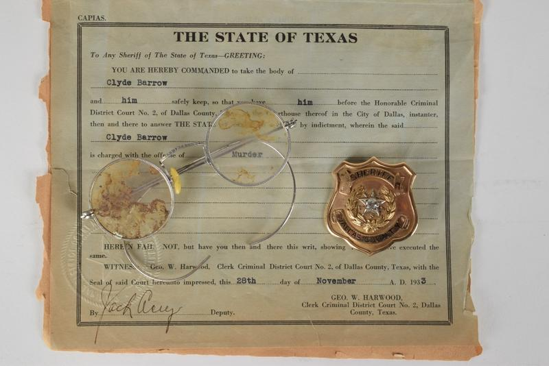 Clyde Barrow's arrest warrant, Bonnie Parker's glasses and Dallas County Sheriff Smoot Schmid's badge.