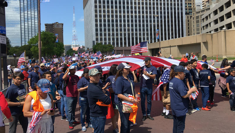 Thousands of marchers carrying U.S. flags turn the corner on the way do Dallas City Hall.