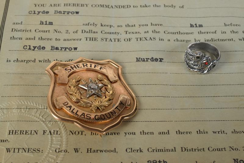 Clyde Barrow's arrest warrant, Bonnie Parker's snake ring and Dallas County Sheriff Smoot Schmid's badge.