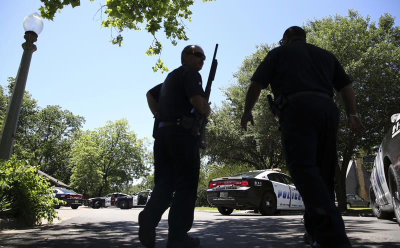 Dallas Police walk a neighborhood a block away from a shooting in Dallas, Monday, May 1, 2017. Authorities said a Dallas paramedic has been shot while responding to a shooting call.