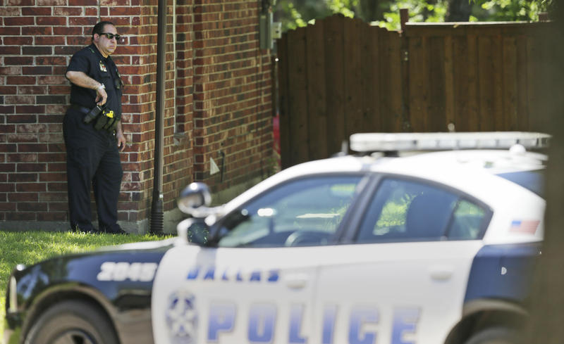 A Dallas Police officer takes a position a block away from a shooting in Dallas, Monday, May 1, 2017. Authorities said a Dallas paramedic has been shot while responding to a shooting call.