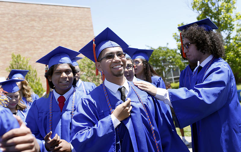 Joel Luera is congratulated by other graduates at W. W. Samuell Early College High School in Dallas.