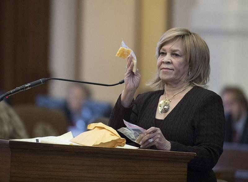 State Rep. Helen Giddings, D-Desoto, holds up a sample of a piece of cheese given to students who lack money to pay for school lunches in Dallas area schools during a personal privilege speech on the House floor May 9, 2017.