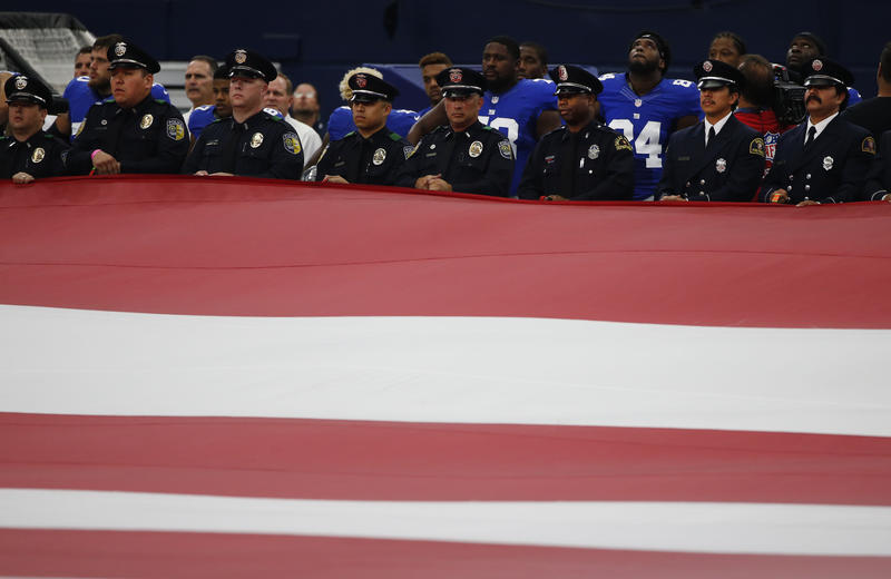 Dallas first responders carry the American flag prior to a Dallas Cowboys game against the New York Giants.