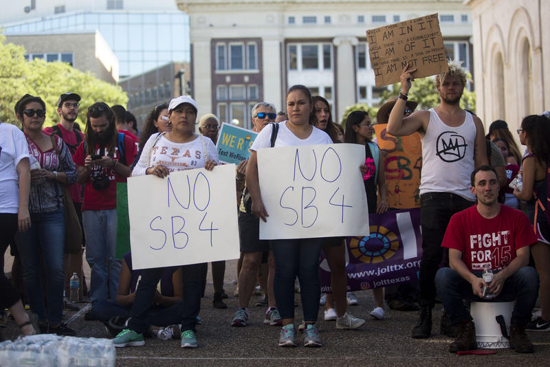 Demonstrators outside the Office of the Governor support a sit-in protest led by City Council Member Greg Casar and dozens of others to protest SB4.