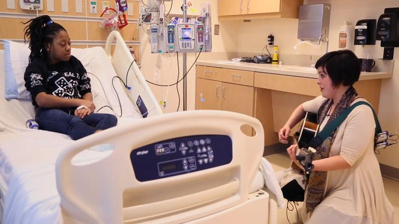 Jude Gonzalez of Dallas' Reinventing Jude performs at the bedside of a patient at Children's Medical Center as part of Musicians On Call.