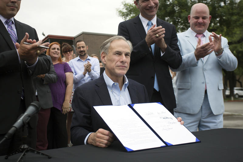 Gov. Greg Abbott signs House Bill 100 into law on May 29, 2017 while the bill's co-sponsors and Uber and Lyft drivers look on. The bill takes ride-hailing regulation statewide and will allow Uber and Lyft to once again operate in Austin.
