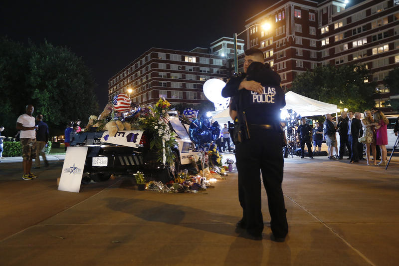 Dallas police officers comfort each other Friday, July 8, 2016, in Dallas in front of police cars decorated as a public memorial in front of police headquarters, in memory of police officers who were killed Thursday, July 7, 2016.