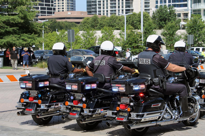 Dallas police officers sit on their motorcycles outside the Morton H. Meyerson Symphony Center on July 12, 2016 during a memorial service for five officers killed in the Dallas police ambush days earlier.