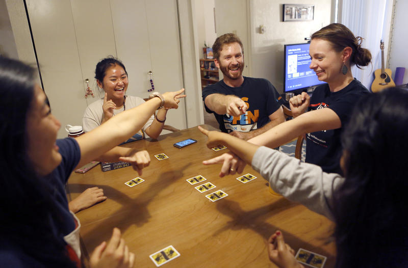 At their home, Alex and Laura Laywell (on the right), play the game, One Night Ultimate Werewolf, with Eh Kaw Thaw (left), 17, who is a refugee born in Thailand, and other neighbors who are refugees from all over the world.