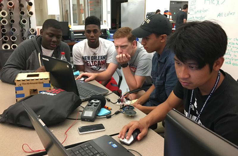 Curriculum creator Parker Holloway (left hand over his mouth) works with the teen team that came up with the louder, longer-lived alarm clock.