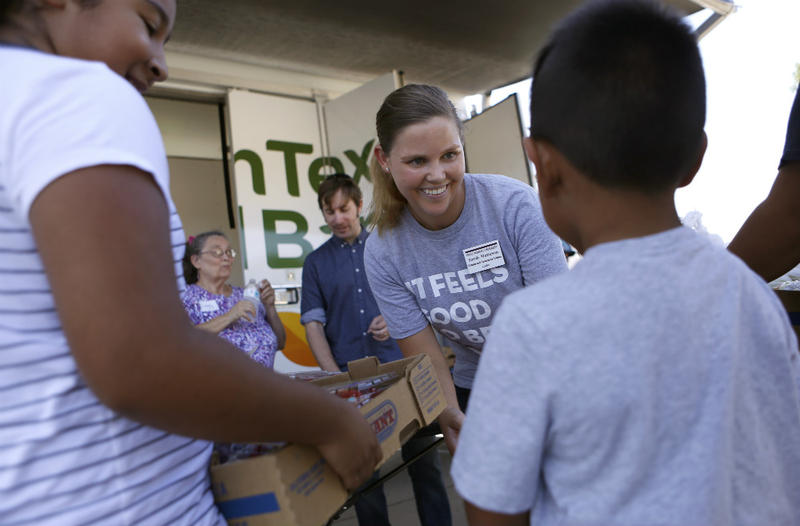 Sarah Matteson greets a family picking up food offered on the Denton campus of Texas Woman's University in partnership with the North Texas Food Bank.
