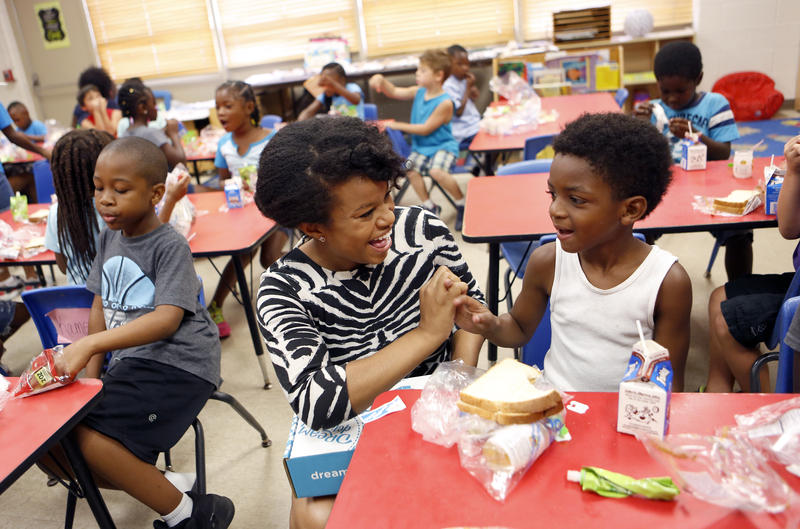 Kam S. Phillips, Founder and Chief Executive Dreamer of Dream Outside the Box, works with children attending a summer camp at Como Community Center in Fort Worth.