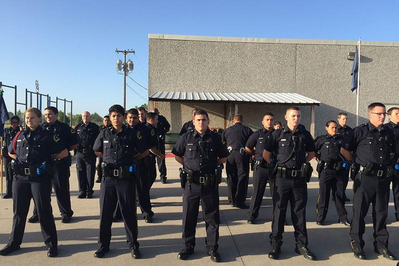 Dallas police academy recruits line up in formation. They'll complete a nine-month training course before going out on patrol.