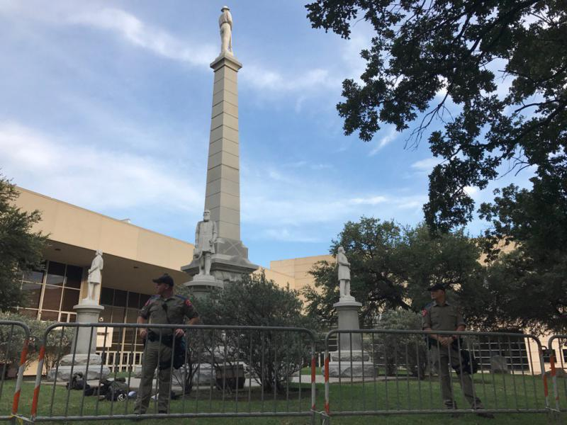 A line of state troopers and barricades surrounds Confederate War Memorial in Dallas ahead of Saturday's rally.