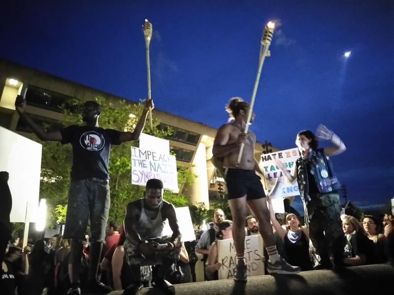 Protesters at City Hall Plaza hold tiki torches, referencing their use by white supremacists in last weekend's protest in Charlottesville, Va.