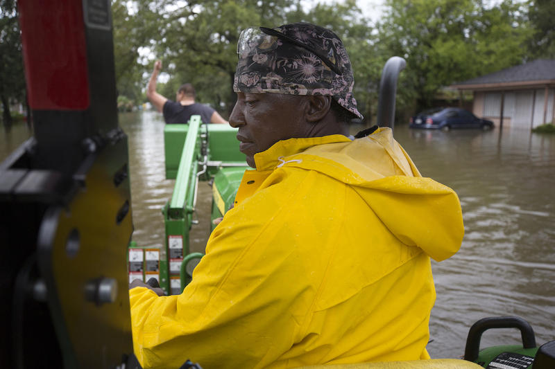 Mel Harris rescued over one hundred residents from the flooded Lakewood community in East Houston, including Raul Garcia, who waves in the front of the tractor.