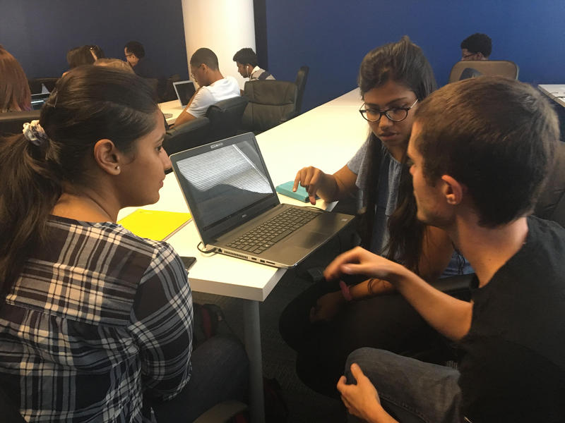 Cody Williams (right) with Coding Dojo works with Pragati Srivastava and Snigdha Goel (left) at an Alexa skills workshop in Dallas.