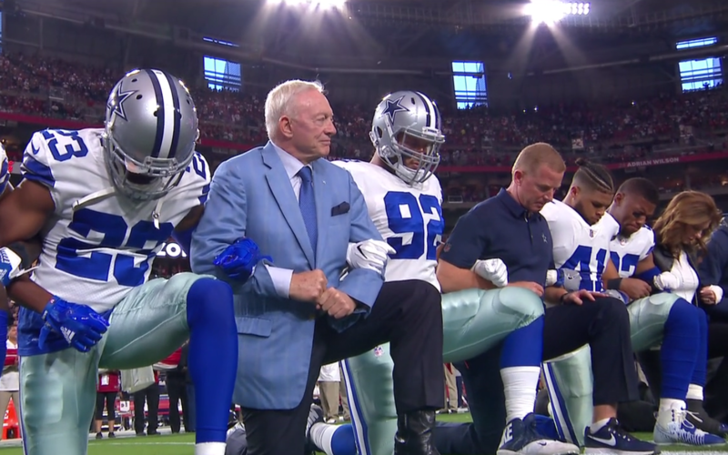 Dallas Cowboys owner Jerry Jones kneels with players and Coach Jason Garrett before the national anthem played at Monday night's game against the Arizona Cardinals.