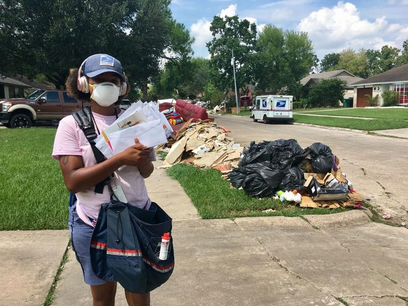 Mail carrier Fateyva Miles  of the U.S. Postal Service makes her rounds in the Scarsdale area of Houston. She's wearing a mask because so much insulation is flying as homeowners rehab their flooded houses.