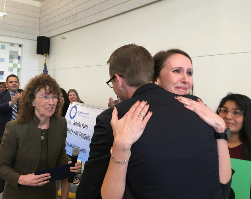 High school English teacher Jennifer Fuller gets a hug from Texas Education Commissioner Mike Morath as Milken Foundation VP Jane Foley looks on. Foley won the award 23 years ago.