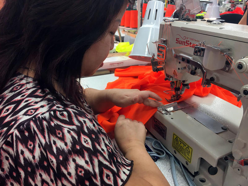 Seamstress Jessie Tran uses a modified sewing machine to help her put the cover stitch on shirts for the Texas Department of Transportation.